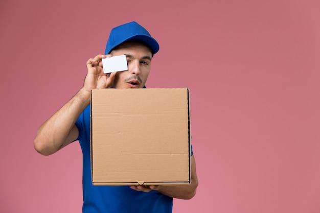 Вид спереди мужской курьер в синей форме, держащий белую карточную коробку с едой на розовой стене, служба доставки униформы работника