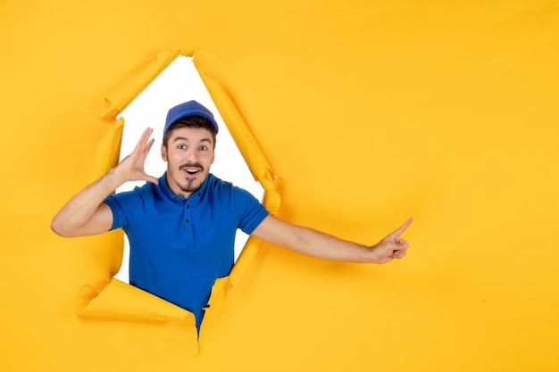 Курьер-мужчина в синей форме на желтом пространстве, вид спереди