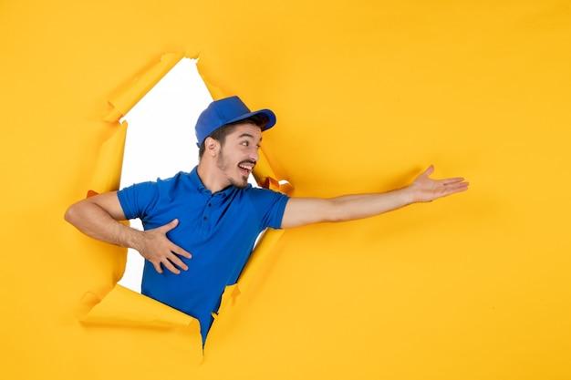 노란색 공간에 파란색 유니폼을 입은 전면 보기 남성 택배