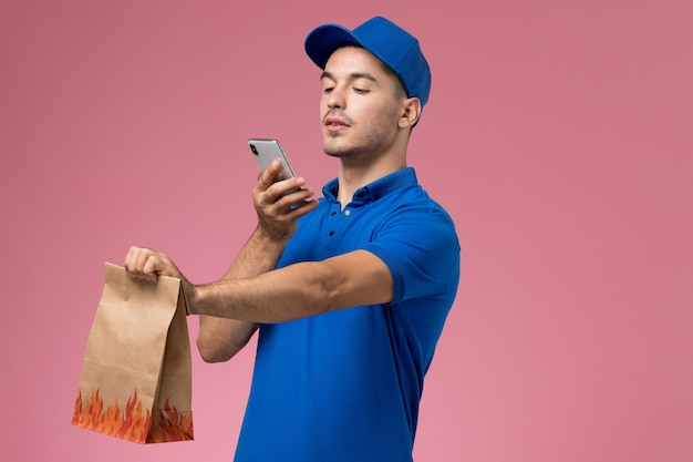 ピンクの壁に食品パッケージの写真を撮る青い制服の正面図男性宅配便、制服の労働者サービスの提供