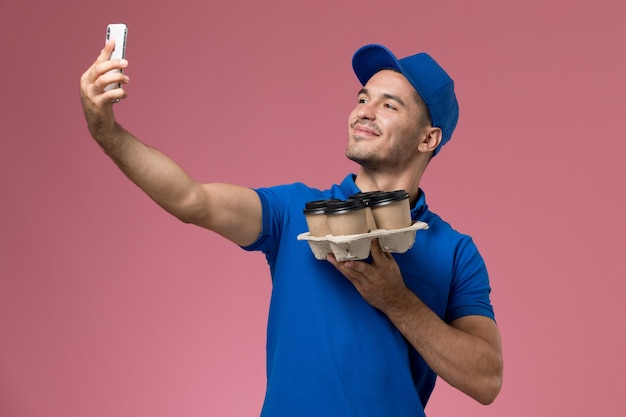 ピンクの壁に配達コーヒーカップ、均一なジョブワーカーサービスの配達でselfieを取る青い制服を着た正面図の男性宅配便