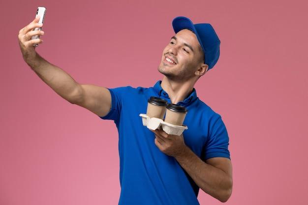 ピンクの壁にコーヒーカップとselfieを取っている青い制服の正面図男性宅配便、均一なサービスの仕事の配達