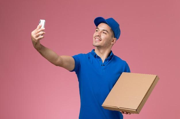 ピンクの壁にフードボックスとselfieを取る青い制服の正面図男性宅配便、均一なサービスの仕事の配達