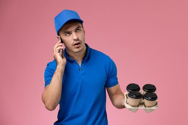 ピンクの壁にコーヒーを持って電話で話している青い制服の正面図男性宅配便、労働者の制服サービスの提供