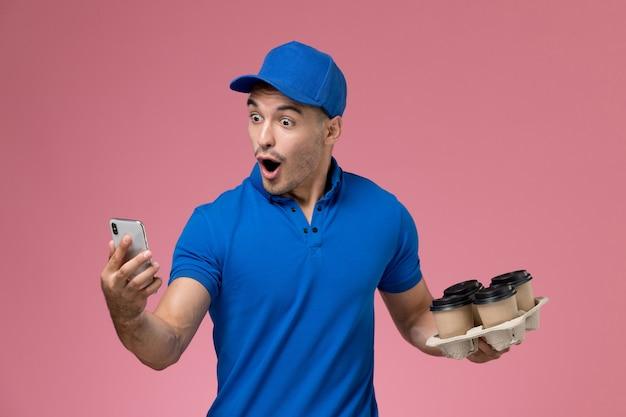 ピンクの壁にコーヒーカップを保持している電話を使用して青い制服を着た正面図の男性宅配便、労働者の制服サービスの提供