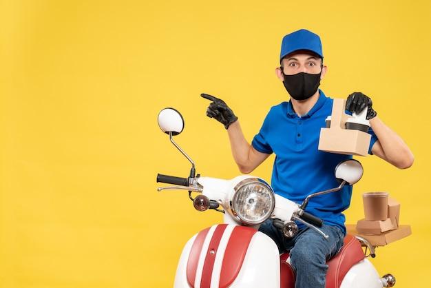 黄色のパンデミックバイクcovid-ジョブ配信ウイルス作業サービスでコーヒーと青い制服を着た正面図の男性宅配便