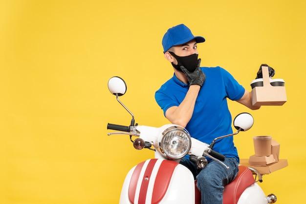 黄色のパンデミックバイクcovid-deliveryウイルス作業サービスでコーヒーと青い制服を着た正面図の男性宅配便