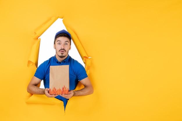 黄色のスペースに食品パッケージと青い制服の正面図男性宅配便