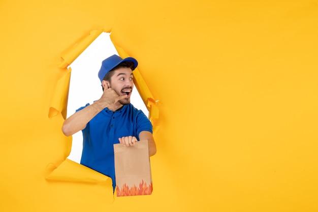 Курьер-мужчина, вид спереди в синей форме с продуктовым пакетом на желтом пространстве