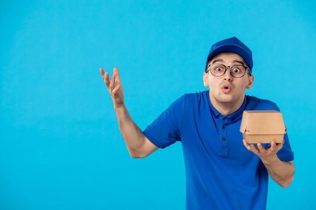 小さな食品パッケージの青い制服を着た正面図の男性宅配便