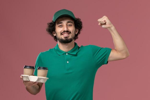 녹색 유니폼과 케이프 핑크 배경 서비스 유니폼 배달 작업 노동자에 flexing 커피 컵을 들고 전면보기 남성 택배