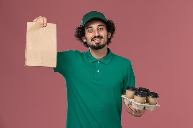 緑の制服とピンクの背景に食品パッケージとコーヒーカップを保持している岬の正面図男性宅配便制服配達仕事労働者男性