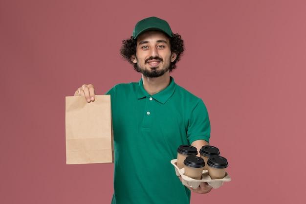 緑の制服とピンクの背景に食品パッケージとコーヒーカップを保持している岬の正面図男性宅配便サービス制服配達労働者男性