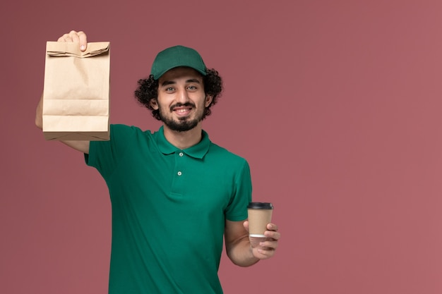 緑の制服とピンクの背景の制服配達サービス会社に配達コーヒーカップと食品パッケージを保持している岬の正面図男性宅配便