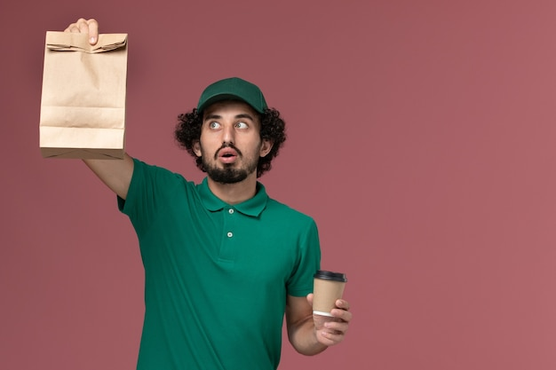緑のユニフォームと薄ピンクの背景に配達コーヒーカップと食品パッケージを保持しているケープの正面図男性宅配便制服配達サービス会社の仕事
