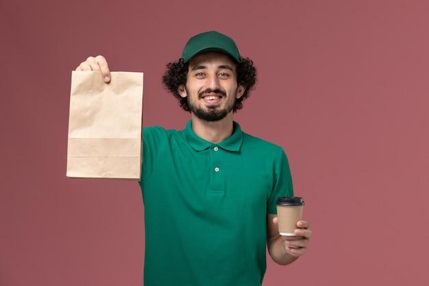 ピンクの背景の制服配達サービスの仕事で配達コーヒーカップと食品パッケージを保持している緑の制服と岬の正面図男性宅配便