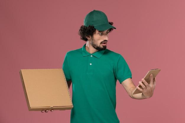 Вид спереди мужчина-курьер в зеленой форме и накидке, держащий блокнот коробки еды доставки с удивленным выражением лица на розовом фоне.