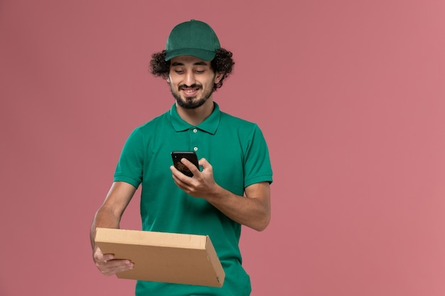 녹색 유니폼과 케이프 핑크 배경 서비스 작업자 유니폼 배달 작업에 사진을 복용 배달 음식 상자를 들고 전면보기 남성 택배
