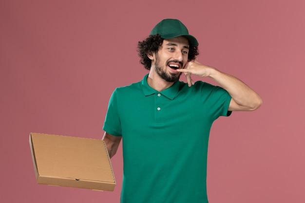 ピンクの背景のサービスワーカーの仕事の制服の配達で電話のポーズを示す緑の制服とケープ保持フードボックスの正面図男性宅配便