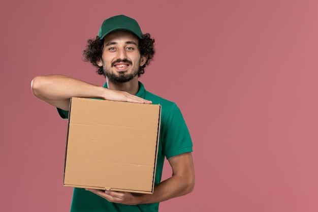 緑の制服とピンクの背景に笑顔でフードボックスを保持している岬の正面図男性宅配便サービス制服配達