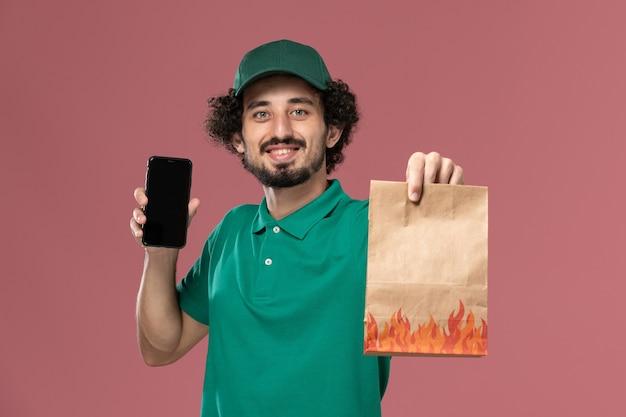 Курьер-мужчина, вид спереди в зеленой форме и плаще, держит пакет с едой и смартфон на розовом фоне.