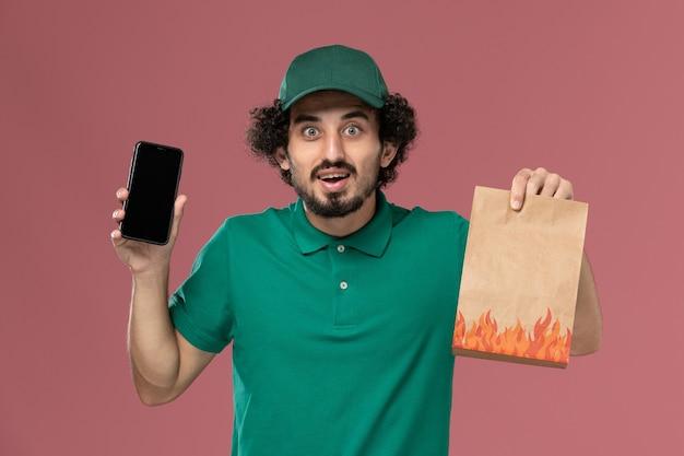 Вид спереди мужчина-курьер в зеленой форме и плаще, держащий пакет с едой и смартфон на розовом фоне, служба доставки униформы мужская работа