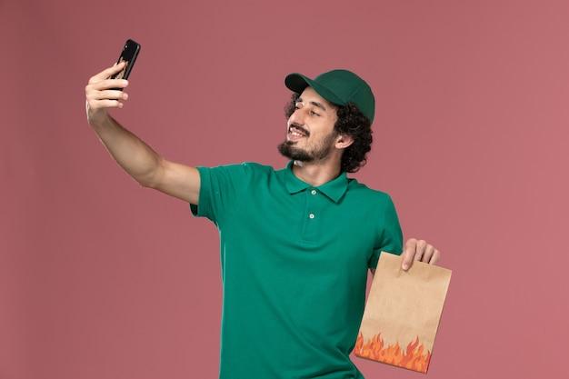 녹색 유니폼과 케이프 음식 패키지를 들고 분홍색 배경 서비스 유니폼 배달 남성 작업에 사진을 찍는 전면보기 남성 택배