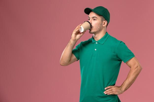 ピンクの背景にコーヒーを飲む緑の制服の正面図男性宅配便