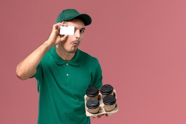 明るいピンクの背景に茶色のコーヒーカップとカードを保持している緑の制服の正面図男性宅配