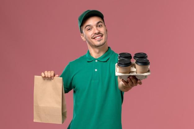 ピンクの背景に茶色のコーヒーカップと食品パッケージを保持している緑の制服の正面図男性宅配便