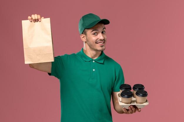 ピンクの背景に笑みを浮かべて茶色のコーヒーカップと食品パッケージを保持している緑の制服を着た正面図男性宅配便