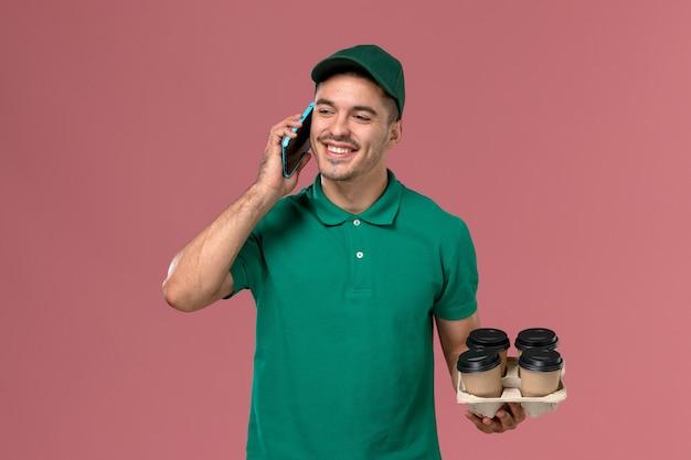 Курьер-мужчина в зеленой форме с коричневыми кофейными чашками разговаривает по телефону на розовом столе, вид спереди