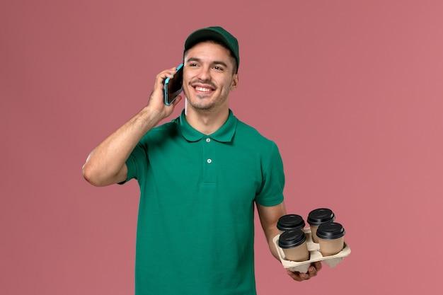 Курьер-мужчина, вид спереди в зеленой форме, держит коричневые кофейные чашки во время разговора по телефону на розовом столе