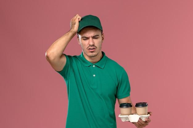 Курьер-мужчина в зеленой форме с коричневыми кофейными чашками и головной болью на розовом фоне, вид спереди