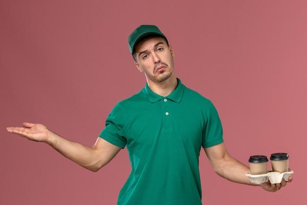 Курьер-мужчина в зеленой форме с коричневыми кофейными чашками и позирует на розовом фоне
