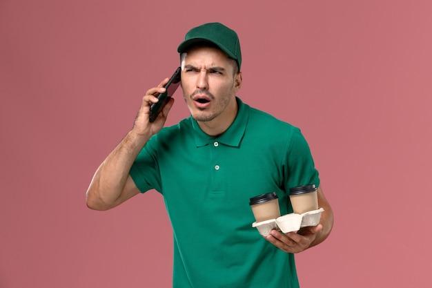 Курьер-мужчина в зеленой форме, вид спереди, держит коричневые кофейные чашки и разговаривает по телефону на розовом фоне