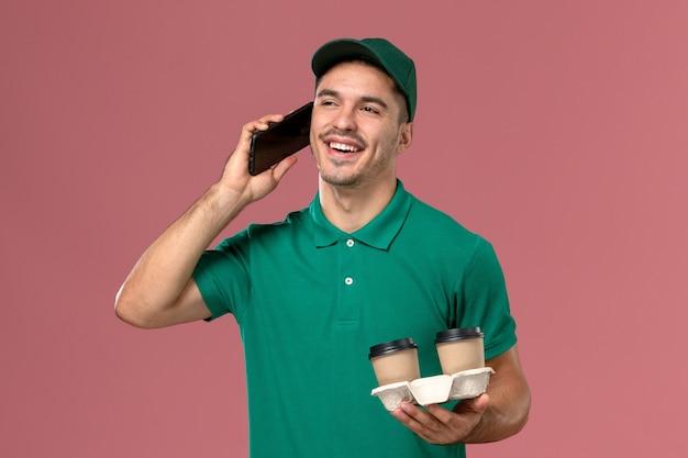 Курьер-мужчина в зеленой форме, вид спереди, держит коричневые кофейные чашки и разговаривает по телефону на розовом столе