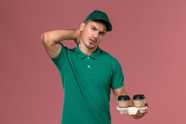 Курьер-мужчина в зеленой форме, держащий коричневые кофейные чашки с болью в шее на розовом фоне, вид спереди