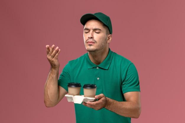 ピンクの背景に香りをかぐ茶色の配達コーヒーカップを保持している緑の制服を着た正面図男性宅配便