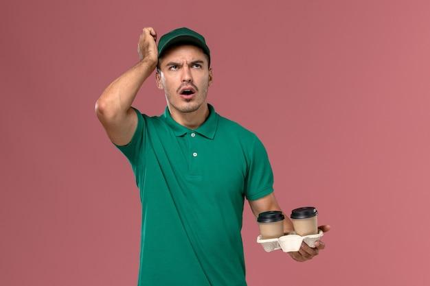 ピンクの背景を考えて茶色の配達コーヒーカップを保持している緑の制服を着た正面図男性宅配便