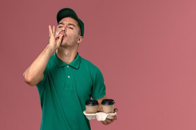 Курьер-мужчина в зеленой форме, держащий коричневые кофейные чашки с вкусным знаком на розовом фоне, вид спереди