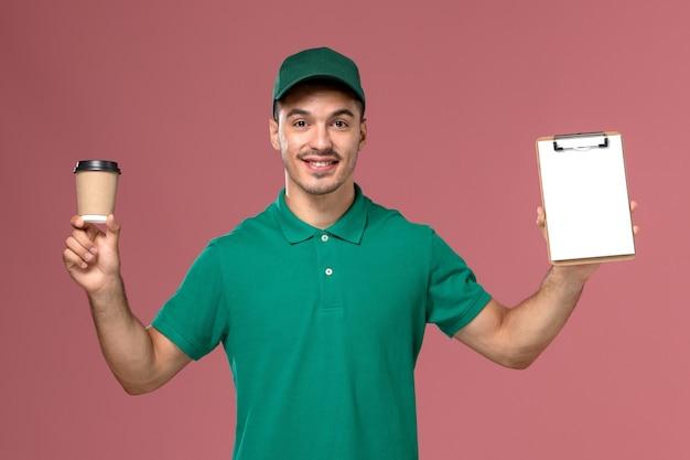 Курьер-мужчина в зеленой форме с чашкой кофе и блокнотом на розовом фоне, вид спереди