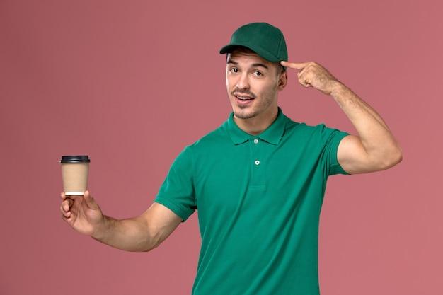 淡いピンクの背景に配達コーヒーカップを保持している緑の制服の正面図男性宅配便