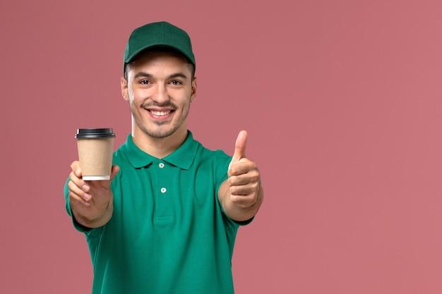Вид спереди мужской курьер в зеленой форме, держащий чашку кофе с улыбкой на розовом фоне