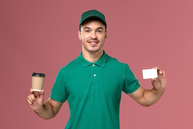 Вид спереди мужской курьер в зеленой форме, держащий чашку кофе с белой карточкой на светло-розовом фоне