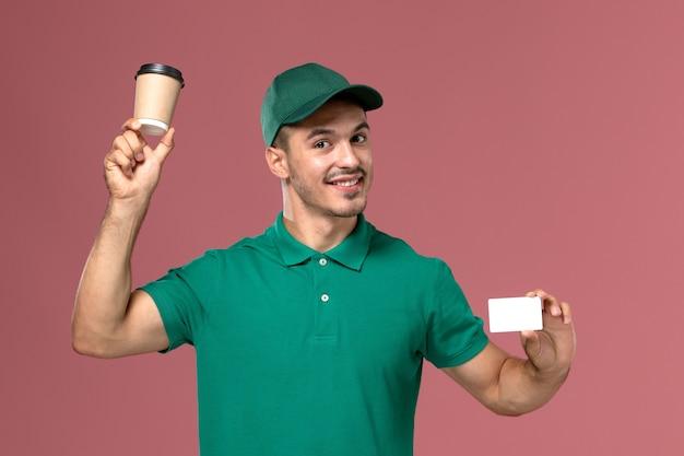 Курьер-мужчина, вид спереди в зеленой форме, держит чашку кофе с белой карточкой на светло-розовом