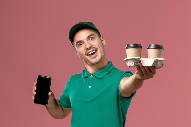 Вид спереди мужской курьер в зеленой форме с доставкой кофейных чашек и телефона на розовом фоне