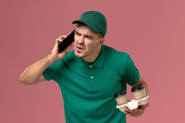 Курьер-мужчина в зеленой униформе с доставкой кофе и разговаривает по телефону на розовом фоне