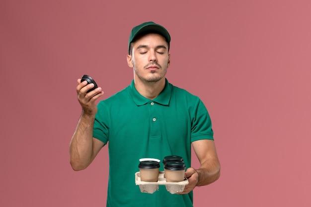 ピンクの机の上に彼らの香りをかぐ配達コーヒーカップを保持している緑の制服を着た正面図男性宅配便