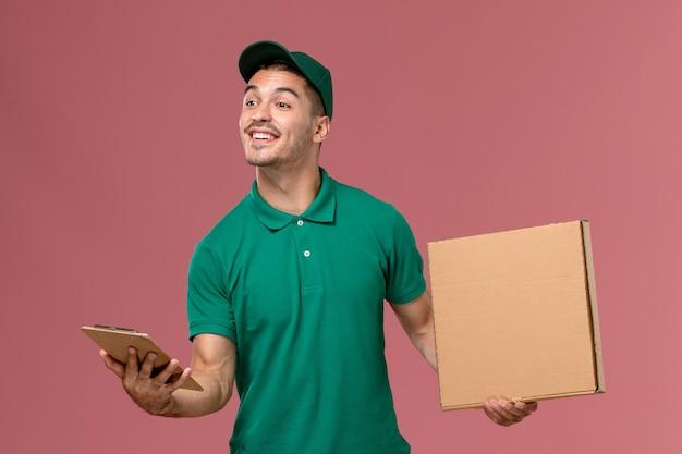 ライトピンクの背景にメモ帳と一緒にフードボックスを保持している緑の制服の正面図男性宅配